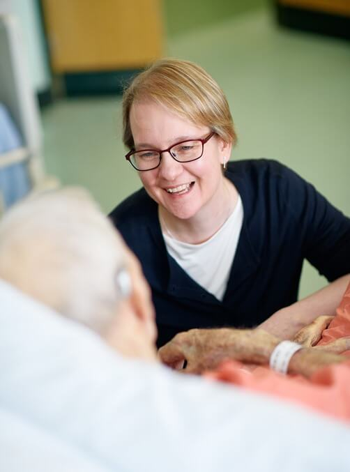 A Northern Care Alliance NHS staff member smiling with an elderly patient