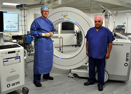 Two members of staff at the Manchester Centre for Clinical Neurosciences with a surgical imaging system